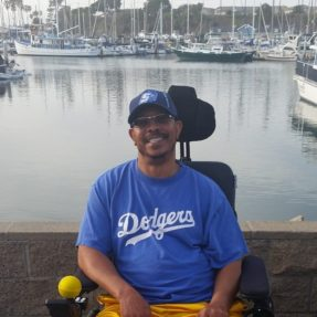 George A. Crockett, Jr. is seated in a wheelchair in front of a body of water.