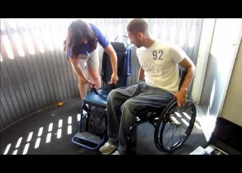 William Bass transfering from his personal wheelchair to an aisle chair.