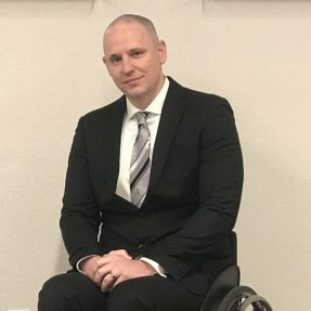 Shaun Castle seated in his wheelchair in front of a wall.
